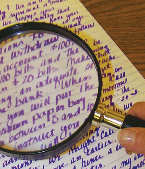 image of a magnifying glass examining handwriting
